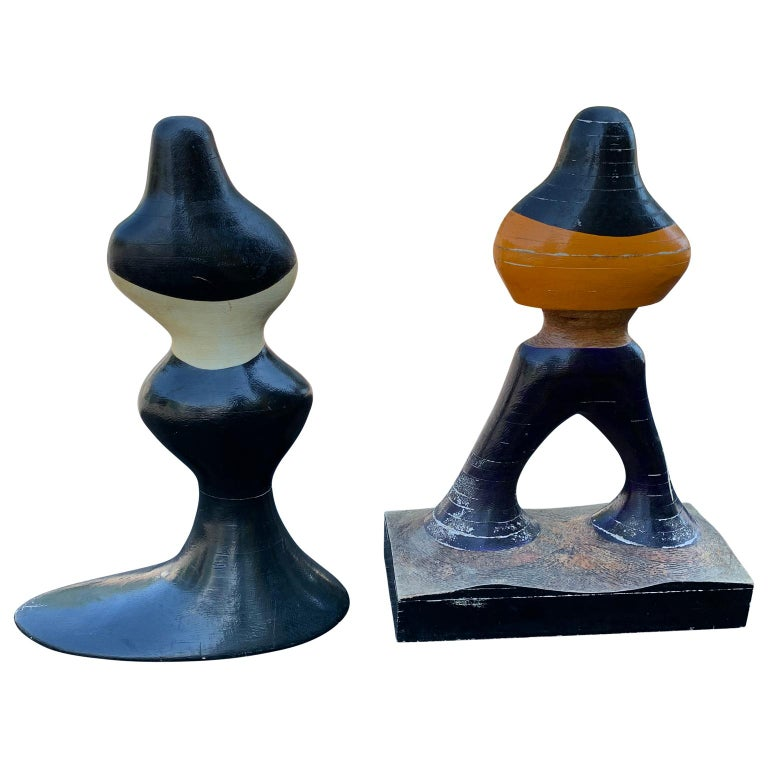 Pair of mid-century figurative sculptures of woman and man in painted wood.