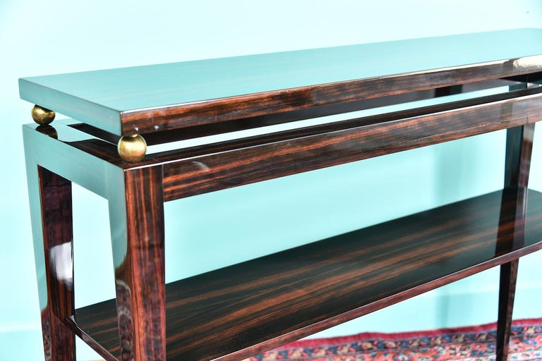 midcentury French consoles in Macassar Console is made out of Macassar wood. It has elongated legs and an extra shelf. There are 4 brass decorative ball between tabletop and legs.   Console is restored. Condition is perfect.   France, circa