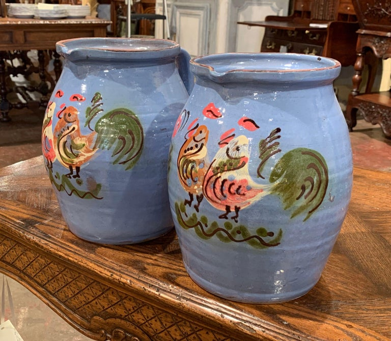 Decorate a wet bar or a kitchen with this matching pair of colorful, vintage water pitchers. Crafted in Normandy, France, circa 1960, each of the large, porcelain jugs features hand painted chicken decor. The farm animals are rendered in a simple,