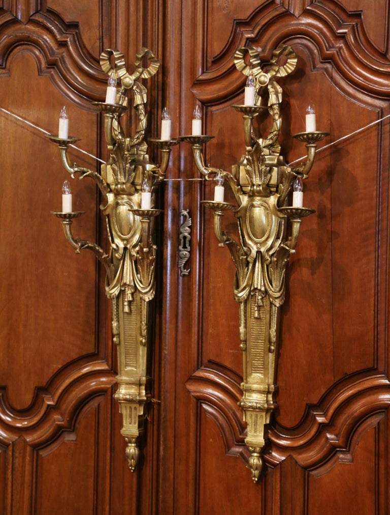 These large and elegant antique bronze sconces were crafted in France, circa 1960. Each wall sconce has five lights newly wired, and features a traditional Louis XVI ribbon bow at the pediment, with acanthus leaves, garland and swag motifs