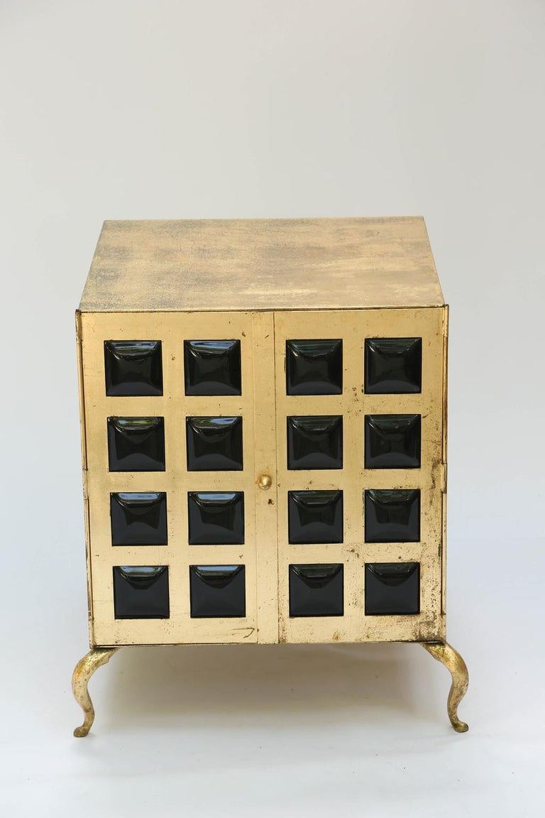 Unusual pair of end tables, each a cabinet of gilt metal, its double doors with grille fronts, inset with