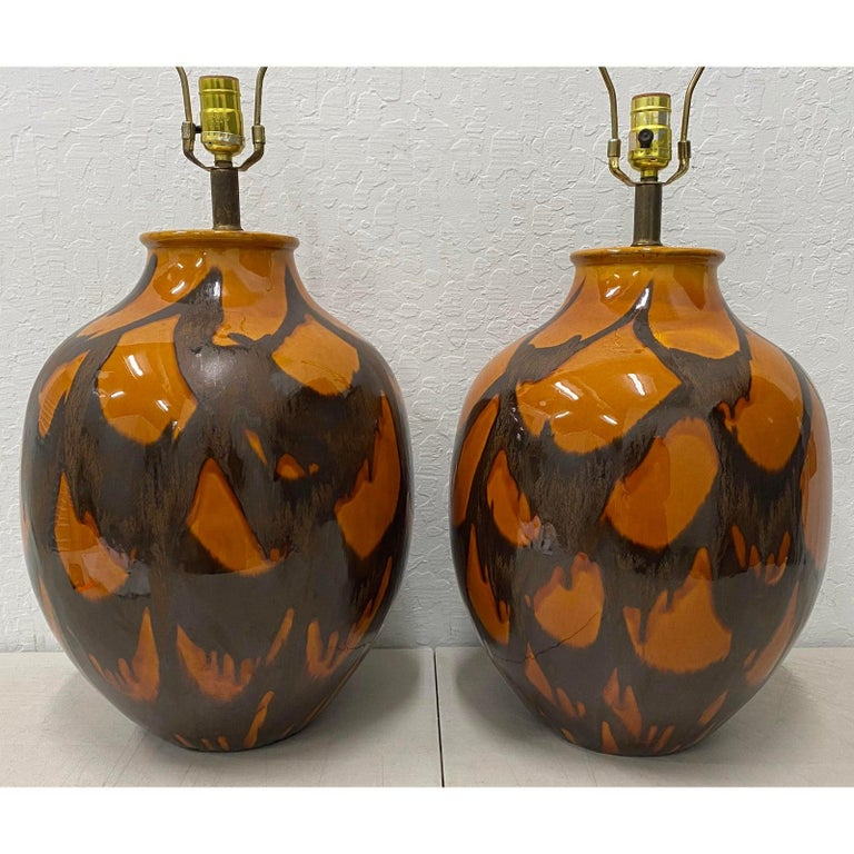 Pair of midcentury glazed ceramic lamps, circa 1970s  Orange and brown glazes - Large Bulbous shape  Measures: 13