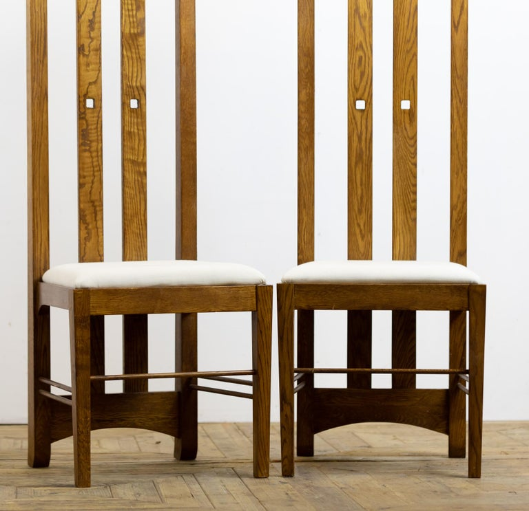 A wonderful pair of mid-20th century light oak chairs in the style of Charles Rennie Mackintosh. The original chairs were designed for Miss Cranston's Ingram Street Tearooms. Upholstered with calico covered drop in seats.