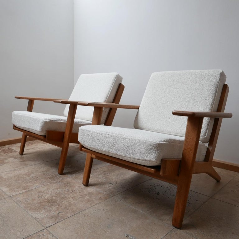Original Hans Wegener midcentury armchairs.  A pair of the much desired GE-209 model.  Swedish, circa 1960s for GETAMA.  Timeless and legendary design.  Completely professionally re-upholstered in white bouclé from Chase