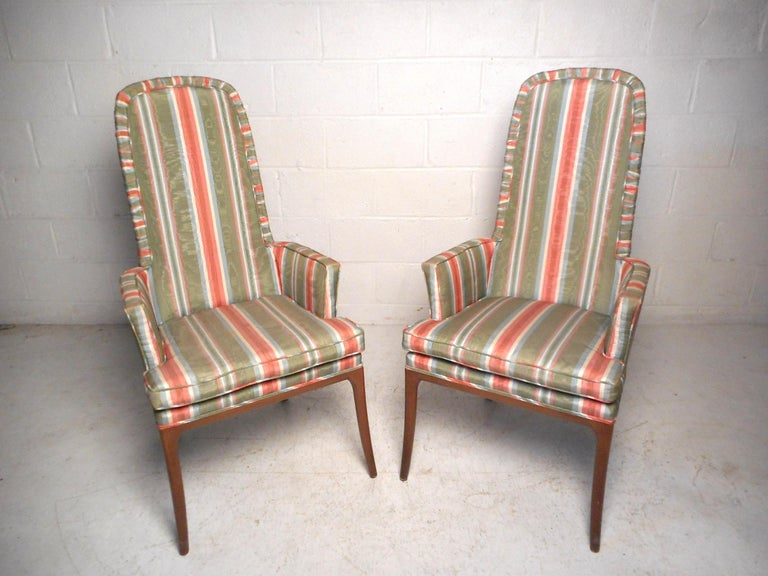 This impressive pair of midcentury chairs feature a vintage striped upholstery and sturdy wooden frames with sleekly splayed legs. This pair would make a great addition to any modern interior's seating arrangement. Please confirm item location with