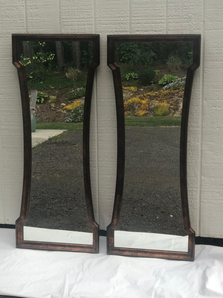 Pair of Mid Century hour glass mirrors attributed to Weiman. Classic oil drip tortoiseshell finish. These dramatic keyhole shaped mirrors could be used above a Dual vanity in a bathroom or entryway in a hall.