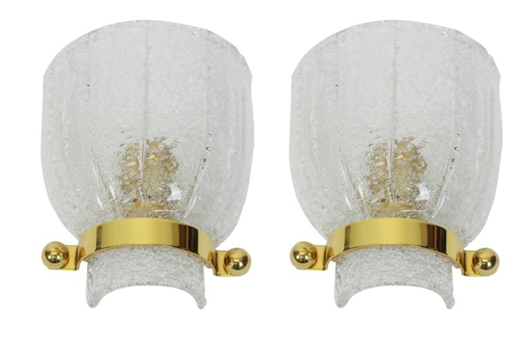 Wonderful pair of midcentury brass wall sconces with ice glass, made by Kalmar, Austria, manufactured, circa 1960-1969.  High quality and in very good condition. Cleaned, well-wired and ready to use.  Each Sconce requires 1 x E14 standard bulbs