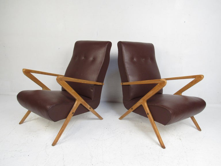 A stunning pair of vintage Italian modern lounge chairs that feature a sculpted teak frame with