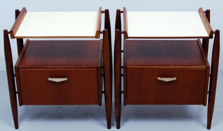 Stylish Italian pair of teak and formica midcentury bedside tables with slim tapered legs on offsets and with brass pulls. Manufactured by Dal Vera Mobili.