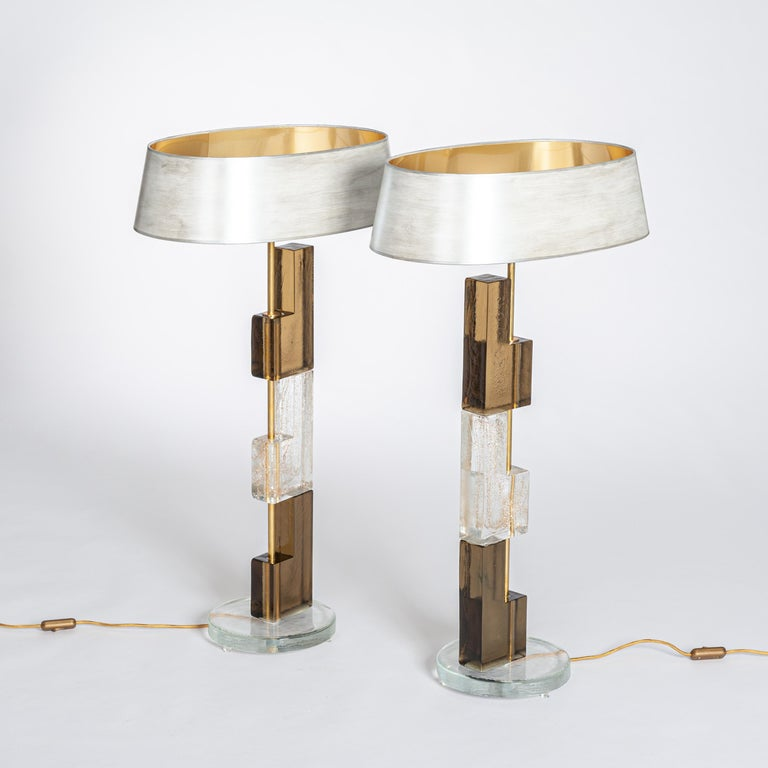 Pair of Murano glass table lamps made of rectangular elements in clear and amber-brown glass on a round base. 