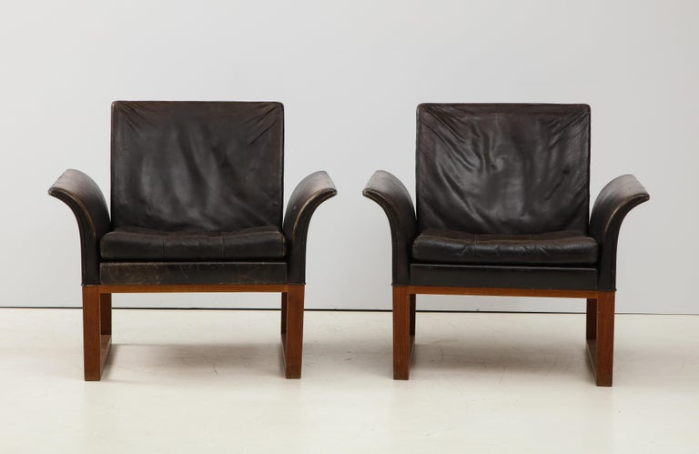 Pair of rare mid-century leather club chairs, Sweden, circa 1950s.   Excellent construction includes clean U-shaped wood legs, button-tufted leather seat cushions, and an elegant curvature in the arms. Gorgeous patina on the leather, which is