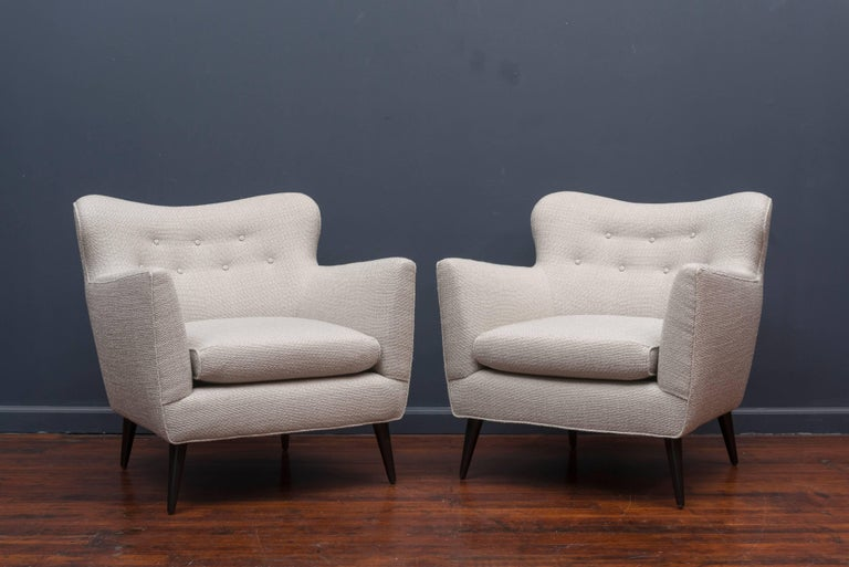 Super pair of mid century lounge chairs newly upholstered in a knobby light silver blend with refinished black lacquer conical legs. Very luxurious and comfy!