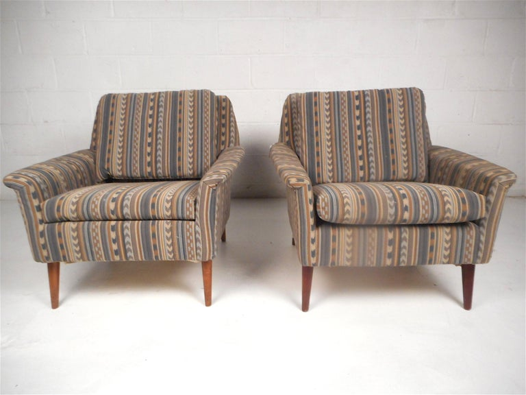 Stylish pair of midcentury lounge chairs. Spacious and comfortable seating with sloped backrests. Sturdy and sleek tapered wooden legs. Covered in a vintage western tapestry style upholstery. Beautiful pair of midcentury chairs sure to impress in