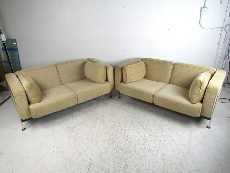 Great pair of Mid-Century Modern loveseats designed by Robert Haussmann. Quality construction with a sturdy polished steel frame spanning the sides and back of the pieces. Upholstered in a vintage beige fabric that has held up very well. This pair