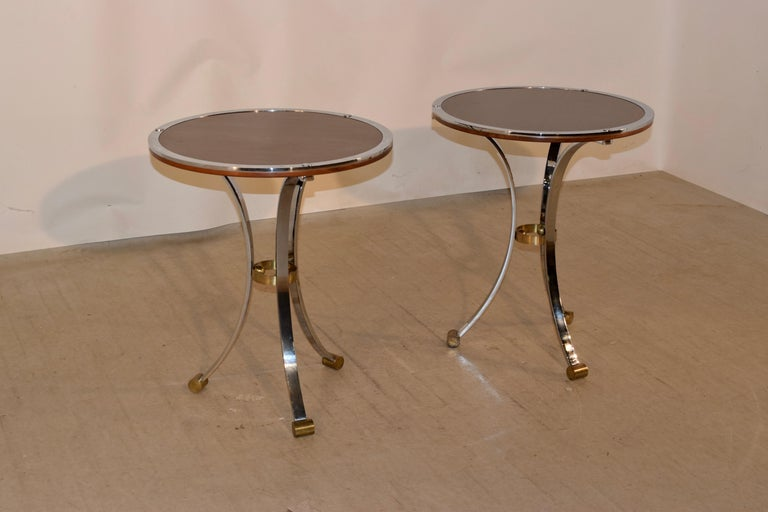 Pair of Mid-Century Modern side tables from England with mahogany tops, banded in chrome. They are supported on chrome legs joined by brass circles and ending in brass feet.