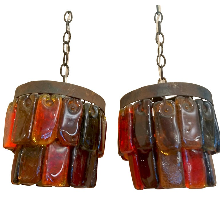 Beautiful pair of pendant lights with two tiers of hand made rectangular glass pieces in assorted colors each, attached to two concentrical iron rings (hold by a chain). The look of the metal is rusty and combines well with the ochre, yellow, orange