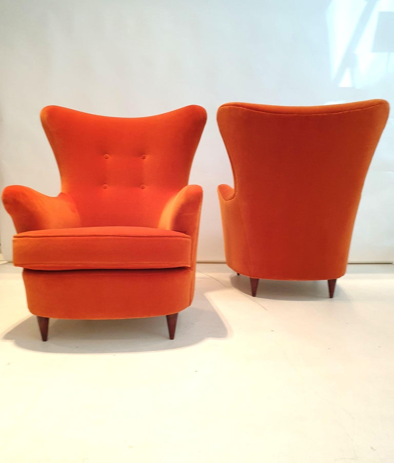 Pair of stylized armchairs with polished wooden feet, reupholstered in burnt orange velvet.