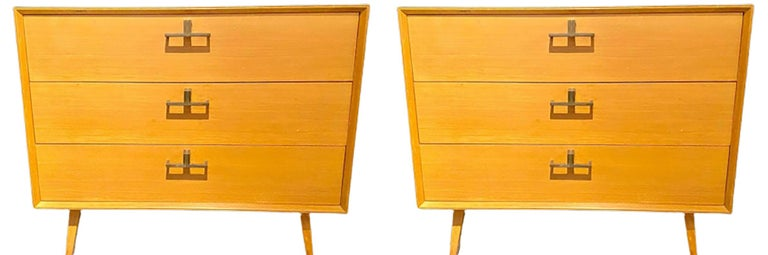 Pair of Mid-Century Modern bachelor chests, commodes, nightstands or dressers. A finely constructed pair of three-drawer commodes, all wood, with brass mounts having a sleek and simply flair. The pair with sprayed legs supporting a large case