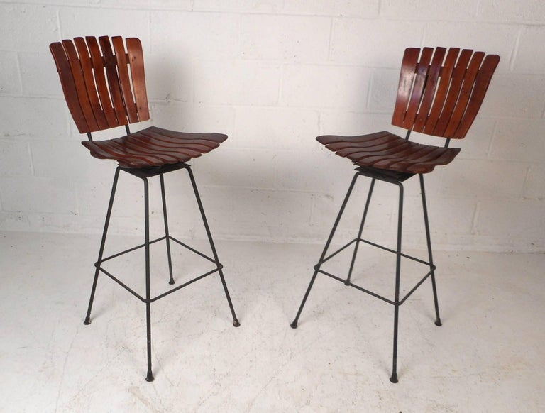 This stunning pair of bar stools feature wrought iron bases and swivel seats. Unique slatted design with the perfect contours for maximum comfort. An elegant dark walnut wood adds to the mid-century appeal. By Arthur Umanoff. Please confirm item