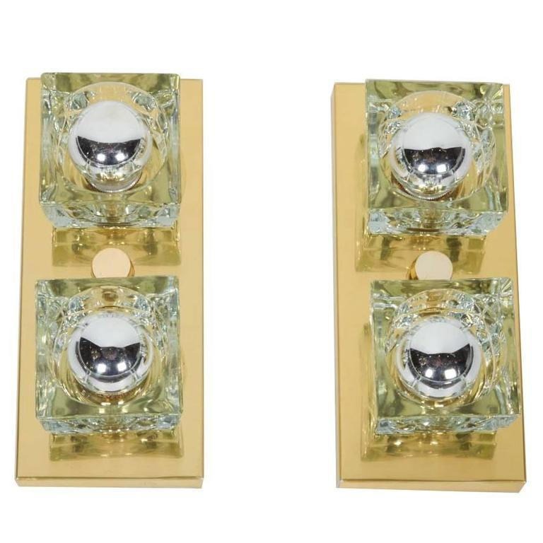 Cubist Mid-Century Modern wall sconces featuring two handcut glass shades each in block forms. Frames are wall-mounted (with vertical and horizontal options), and are finished in polished brass with matching fittings.