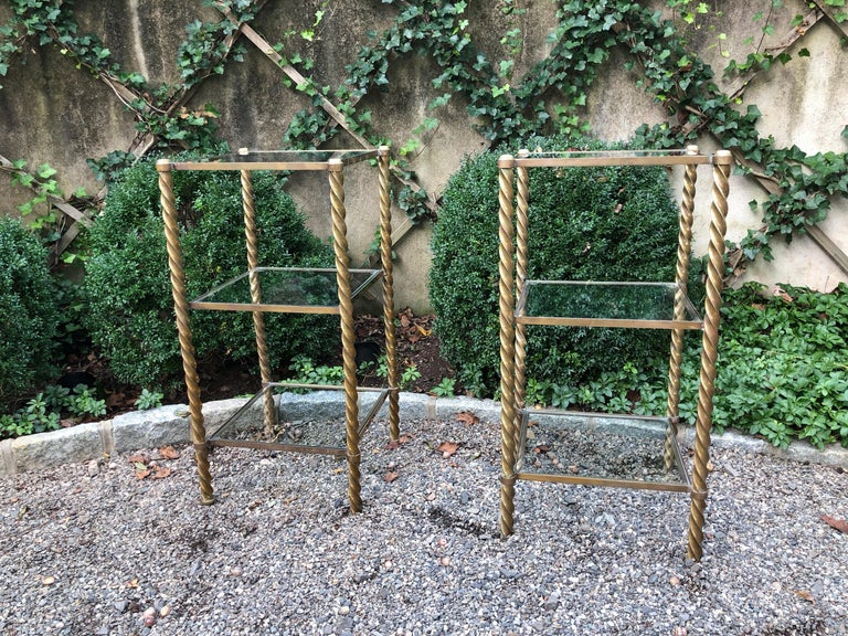 Pair of very stylish Mid-Century Modern brass and glass 3-tiered étagères having shelves with inset glass flanked by barley twist supports. They are quite heavy as the brass is thick and substantial.