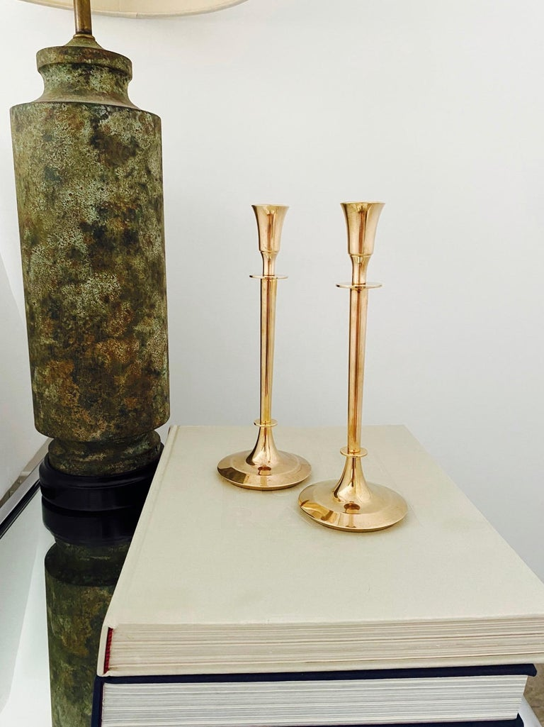 Pair of Swedish Mid-Century Modern candle holders cast in solid brass. The candlesticks have chic narrow stems with minimalist forms. The circular bases are tapered with beveled edges. Makes a beautiful addition to any tableware setting.