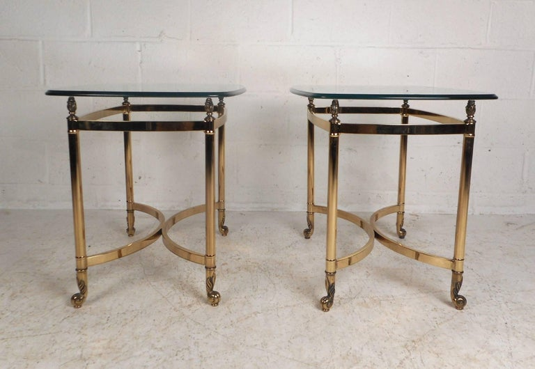 Unique pair of vintage modern side tables with heavy brass bases and thick bevelled glass tops. Sleek design with an ellipse shape in the centre of the base and sculpted feet. These wonderful midcentury tables have remarkable etched detail on the