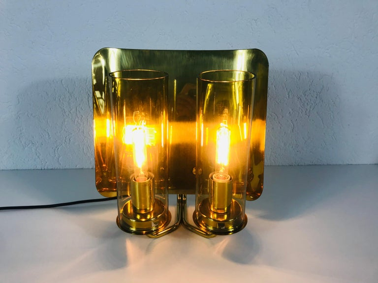 A beautiful pair of brass wall lamps made in Sweden in the 1960s. The pair has an amazing midcentury design. It is made of brass and amber glass and fits perfectly into a living room. The glass shade is very thin and elegant.  The light requires