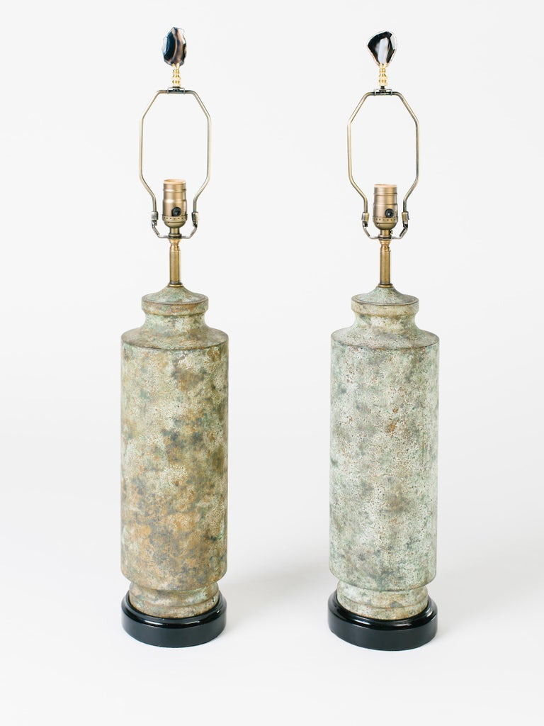 Pair of Mid-Century Modern lamps with Brutalist design. Made of cast iron with Asian pagoda column design. Metal has been purposely oxidized for a distressed look reminiscent of camouflage pattern in hues of moss green and brown. Newly restored