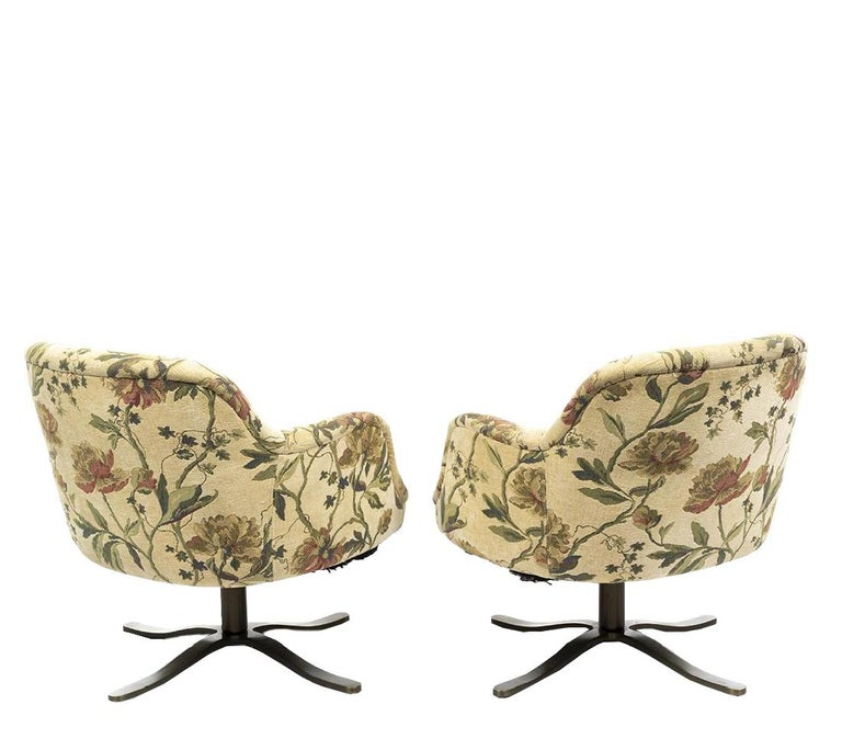 Pair of Mid-Century Modern swivel bucket chairs designed by Nicos Zographos. Slightly worn under each seat; four star stainless steep alpha bases.