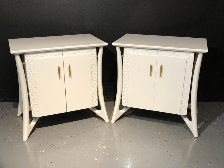 Pair of Mid-Century Modern chests, nightstands or end tables. A recently pale gray lacquered pair of nightstands or end tables. Each case having two doors with flanking carved mesh framing and gilt metal pulls leading to an open compartment with one