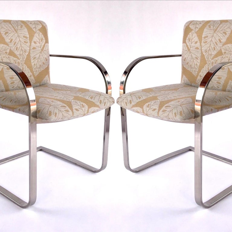 Mid-Century Modern desk chairs or side chairs with cantilevered steel frames in chrome. Chairs have streamlined profile with curved armrests and floating seat design. Newly upholstered in bold handwoven fabric with tropical leaf print in