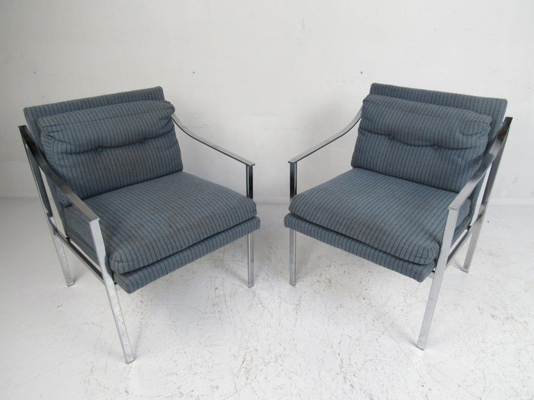 This stunning vintage modern pair of lounge chairs feature a heavy flat bar chrome frame and thick padded seats. The unique sloped armrests and tufted backrest add to the midcentury appeal. This exquisite pair of Milo Baughman style lounge chairs