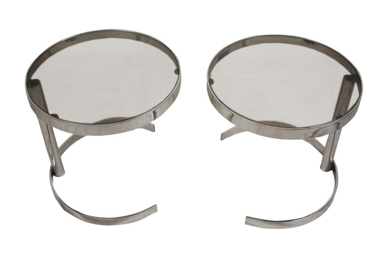 A pair of Mid-Century Modern chrome side tables with smoked glass and asymmetrical stand. Could also be used as a coffee table when combined.