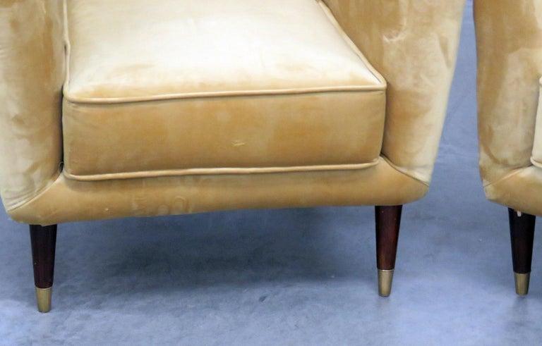 Pair of Mid-Century Modern velvet club chairs with brass sabots.