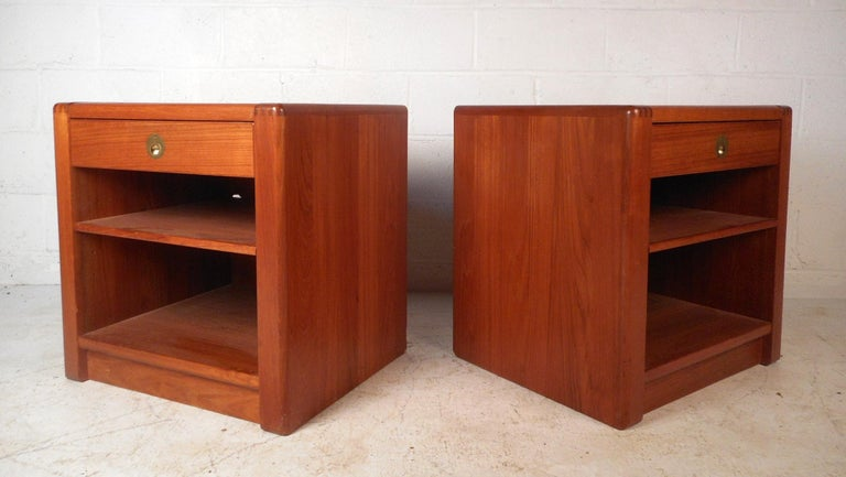 This beautiful pair of Danish teak nightstands have a sleek design and plenty of storage space. The drawers feature unique recessed brass pulls. These nightstands boast rounded off dovetail joints, adding style to the sturdy construction. Please