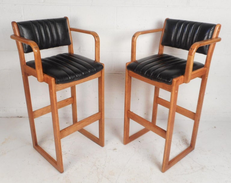 This beautiful pair of Danish modern bar stools feature a teak frame with sled legs. Unique design with high rounded arm rests, an angled backrest, and a black vinyl covered seat. This stunning pair offers plenty of comfort without sacrificing style