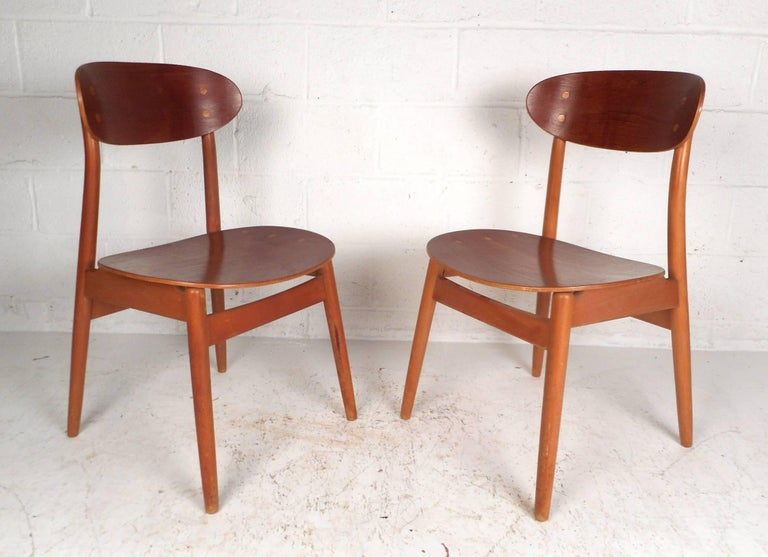 Wonderful pair of vintage modern chairs with curved wing style back rests and contoured seats. Sturdy Danish design with tapered legs and dovetail construction. This unique pair of midcentury side chairs offer plenty of comfort without sacrificing
