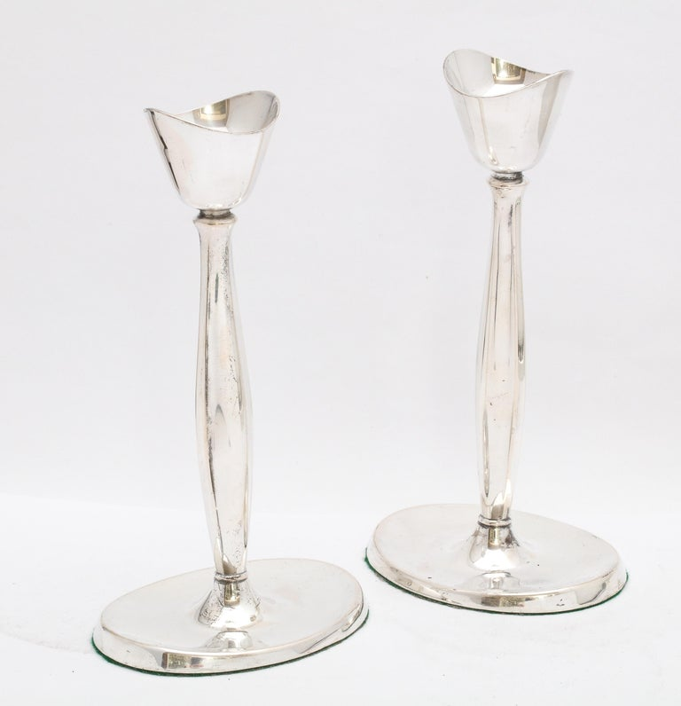Pair of Mid-Century Modern, sterling silver candlesticks, Denmark, Ca. 1940's, Cohr - maker. Graceful design, each candlestick having an oval base and lightly fluted column. Each candlestick measures 7 1/2 inches high x 4 inches wide (across oval