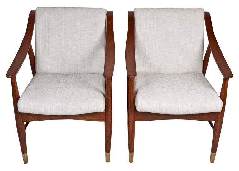 A pair of Danish teak side chairs in the style of Louis Van Teeffelen, Mid-Century Modern. Reupholstered with an off-white silk and linen blend. Brass feet.