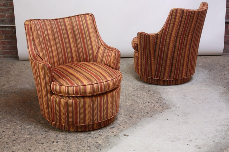 Small scale Mid-Century Modern armchairs with swivel function reminiscent of Edward Wormley's design for Dunbar but unmarked. The chairs and swivel bases were reupholstered (likely in the 1970s or 1980s), and there is slight wear commensurate with