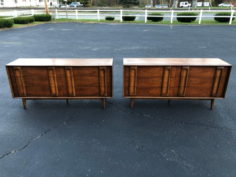 Pair of Mid-Century Modern dressers by Lane. Sculptural walnut dressers with a soft burl wood panel at the handles. Classic and timeless design. Use as a dresser or as a server /credenza. 6 drawers per dresser. We can break up the set if you want to