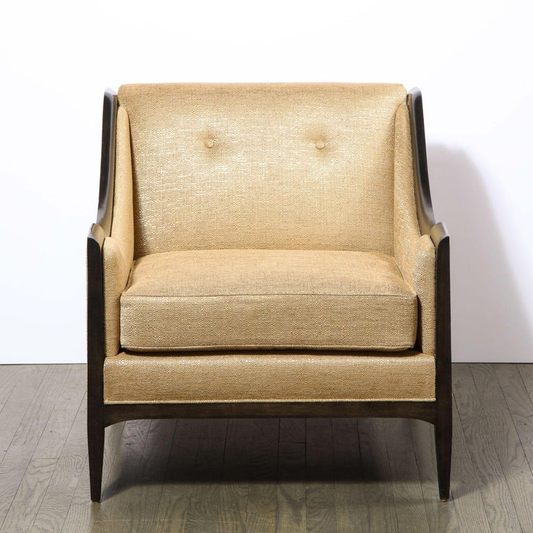 This elegant pair of Mid-Century Modern club chairs were realized in the United States circa 1960. They offer arched hind legs; tapered cylindrical front legs; a square back; scalloped sides framed in hand rubbed ebonized walnut. Additionally, they