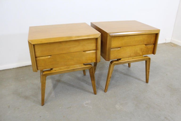 Offered is a pair of midcentury nightstands with sleek lines designed by American designer Edmond J. Spence. Made from yellow birch, these stands feature beautifully sculpted legs and two dovetailed drawers with hidden pulls. They have been