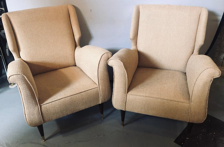 Pair of Mid-Century Modern Gio Ponti style arm or wingback chairs. These finely detailed sleek and stylish armchairs depict this iconic designers style for flair and simplicity at his highest level. The tapering mahogany legs sitting on brass sabots