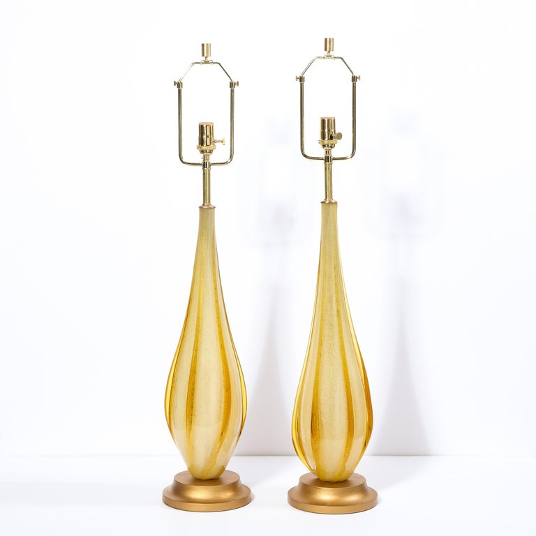 This stunning pair of Mid-Century Modern table lamps were realized in Murano, Italy- the island off the coast of Venice renowned for centuries for its superlative glass production- circa 1960. They features honey hued tear drop bodies with raised