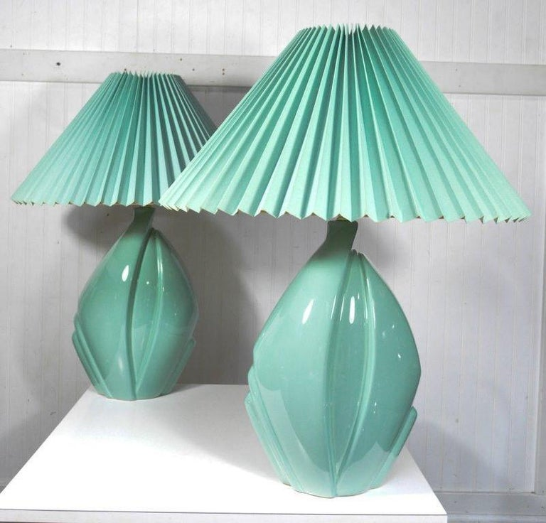 Pair of lovely vintage Mid-Century Modern / Hollywood Regency seafoam green / bluish pottery sculptural table lamps by Harris lamps, circa 1990. The lamps feature great lines and original large pleated shades. Wired for three-way bulbs, circa 1990.