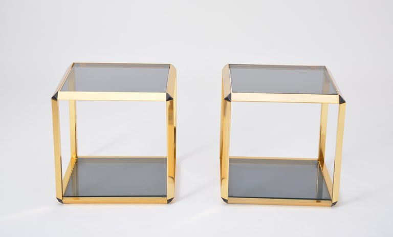 Pair of Mid-Century Modern Italian gold-rimmed metal and glass side tables  Beautiful and rare pair of low tables in gold-colored steel frames with smoked glass tops produced in the 1970s in Italy. Gold color version  Glasses, hooks and suction