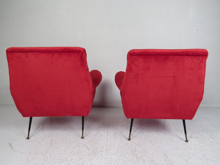 This beautiful pair of vintage modern lounge chairs feature thick padded seating covered in elegant ruby red upholstery. A sleek and comfortable low sitting design that has splayed metal legs with brass feet. The overstuffed armrests and wide