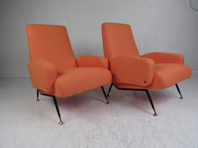A beautiful pair of vintage modern Italian lounge chairs with unusual sloped armrests and splayed metal legs. An extremely comfortable pair with thick padded seating covered in plush orange fabric. This stylish pair of armchairs make the perfect